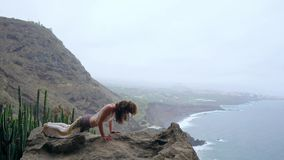 Young Caucasian woman performing upward facing dog pose outdoors