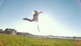 Young caucasian woman performs acrobatic jumps outdoors at sunny day. Slow motion stock video