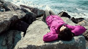 Young Caucasian woman with pink coat lying on the rocks near the wavy sea. On a sunny winter day stock footage