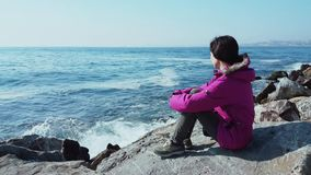Young Caucasian woman with pink coat sitting on the rocks near the wavy sea. On a sunny winter day stock footage