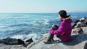 Young Caucasian woman with pink coat sitting on the rocks near the wavy sea. On a sunny winter day stock video footage