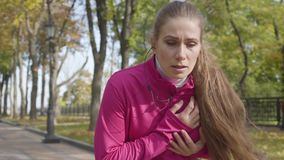Young Caucasian woman in pink sportswear stopping during the run because of chest pain. Female runner feeling bad during. The morning training in the autumn stock video