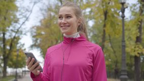 Young Caucasian woman in pink sportswear turning on music in her headphones and starting running. Female runner training. In the morning outdoors. Sports stock video footage