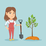 Young caucasian woman planting a tree. Young smiling caucasian woman planting a tree. Cheerful woman standing with shovel near newly planted tree. Concept of Stock Image