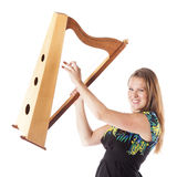 Young caucasian woman plays small harp in studio against white b Royalty Free Stock Image
