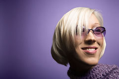 Young Caucasian woman portrait. Portrait of smiling young adult Caucasian blond woman on purple background wearing sunglasses and scarf Royalty Free Stock Photography