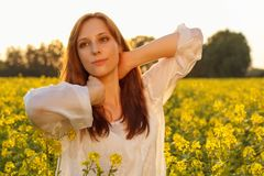 Young caucasian woman is posing in the field of stock image