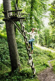 Young caucasian woman posing on the wooden ladder, natural scene Stock Photography