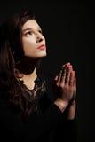 Young caucasian woman praying. Closeup portrait of a young caucasian woman praying royalty free stock images