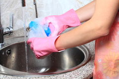 Young caucasian woman in protective gloves washing dishes. Royalty Free Stock Photos