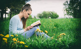 Young caucasian woman reading a book outdoor Stock Images