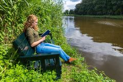Dutch woman reading book on bench at water Royalty Free Stock Photos