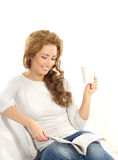 A young Caucasian woman reading and drinking Stock Image