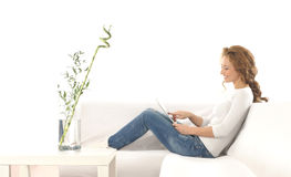 A young Caucasian woman relaxing on a sofa Stock Photography
