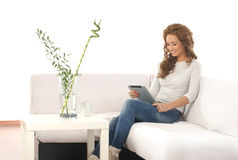 A young Caucasian woman relaxing on a white sofa Royalty Free Stock Photography