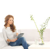 A young Caucasian woman relaxing on a white sofa stock image