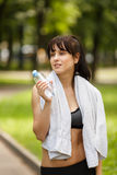 Young caucasian woman resting with bottle of water after workout Royalty Free Stock Photos
