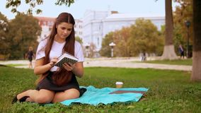 Girl reading book on lawn stock video