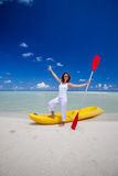 Young caucasian woman rests at beach near kayak Stock Photography