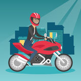 Young caucasian woman riding a motorcycle at night. Young happy caucasian woman in helmet riding a motorcycle on the background of night city. Motorcyclist Stock Photo