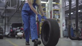 Young caucasian woman rolling tire in repair shop. Smiling female auto mechanic at workplace. Camera zooming down