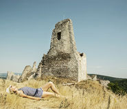 Young caucasian woman in a sailor outfit lying on the dry grass Royalty Free Stock Photo