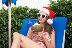 Young Caucasian Woman in Santa Claus Hat Drinking Coconut on Sunbed. Young Caucasian Woman in Santa Claus Hat and Sunglasses Drinking Coconut on Sunbed Royalty Free Stock Images