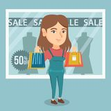 Young caucasian woman shopping on sale. Young caucasian woman showing shopping bags in front of shop window with sale sign. Woman standing on the background of Stock Image