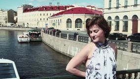Young woman enjoying sun beams at city bridge over river. Young caucasian woman with short hair wearing colorful dress enjoying sun beams at city bridge over stock video footage