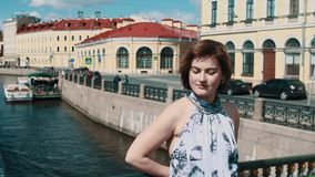 Young woman looking around smiling at city bridge over river. Young caucasian woman with short hair wearing colorful dress looking around smiling at city bridge stock video