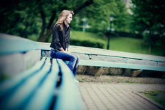 Young caucasian woman sitting alone on a bench in depression. Royalty Free Stock Images