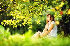 Young caucasian woman is sitting below the apple tree Royalty Free Stock Image