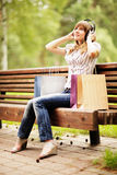 Young caucasian woman sitting on park bench with shopping bags and listening to the music using big headphones. Stock Image