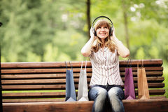 Young caucasian woman sitting on park bench with shopping bags and listening to the music using big headphones. Stock Photos
