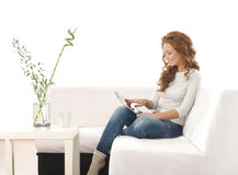 A young Caucasian woman sitting on a white sofa Royalty Free Stock Photos