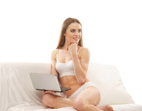 A young Caucasian woman sitting on a white sofa Stock Images