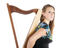 Young caucasian woman with small harp in studio against white ba Royalty Free Stock Image