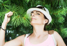 Young caucasian woman sniffs green needles of conifer tree stock photo