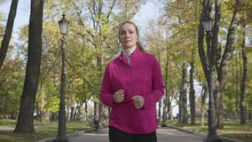 Young Caucasian woman in sportswear and headphones running in the autumn park. Female runner training in the morning. Outdoors. Sports concept stock footage