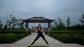 Young caucasian woman in sportswear relaxing by practicing yoga barefoot in the city park. Sunrise background. Slow royalty free stock photography