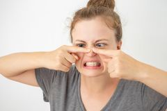 Young caucasian woman squeezing a pimple on her nose, funny facial expression stock photography