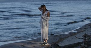 Young Caucasian woman standing on the beach and looking at waves. Thoughtful girl spending summer evening outdoors. Young Caucasian woman standing on the beach stock footage