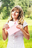 Young caucasian woman standing on blurred green summer background. Holding a blank letter in pink envelope. Letter and envelope co Royalty Free Stock Images