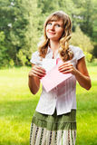 Young caucasian woman standing on blurred green summer background. Holding a blank letter in pink envelope. Letter and envelope co Royalty Free Stock Photography