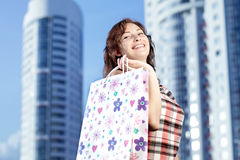 Young caucasian woman standing in city with shopping bags. Smiling and looking at camera. Stock Photos