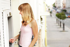 Young caucasian woman standing near an ATM holding a credit card. Royalty Free Stock Photos