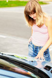 Young caucasian woman standing near a car and looking at map. Stock Images