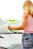 Young caucasian woman standing near a car and looking at map. Royalty Free Stock Images