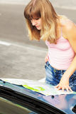 Young caucasian woman standing near a car and looking at map. Royalty Free Stock Photo