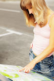 Young caucasian woman standing near a car and looking at map. Stock Photos